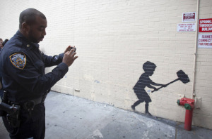 New York City cop taking a picture with his phone of Banksy graffiti art.