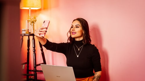 Social media influencer taking a selfie with an iPhone